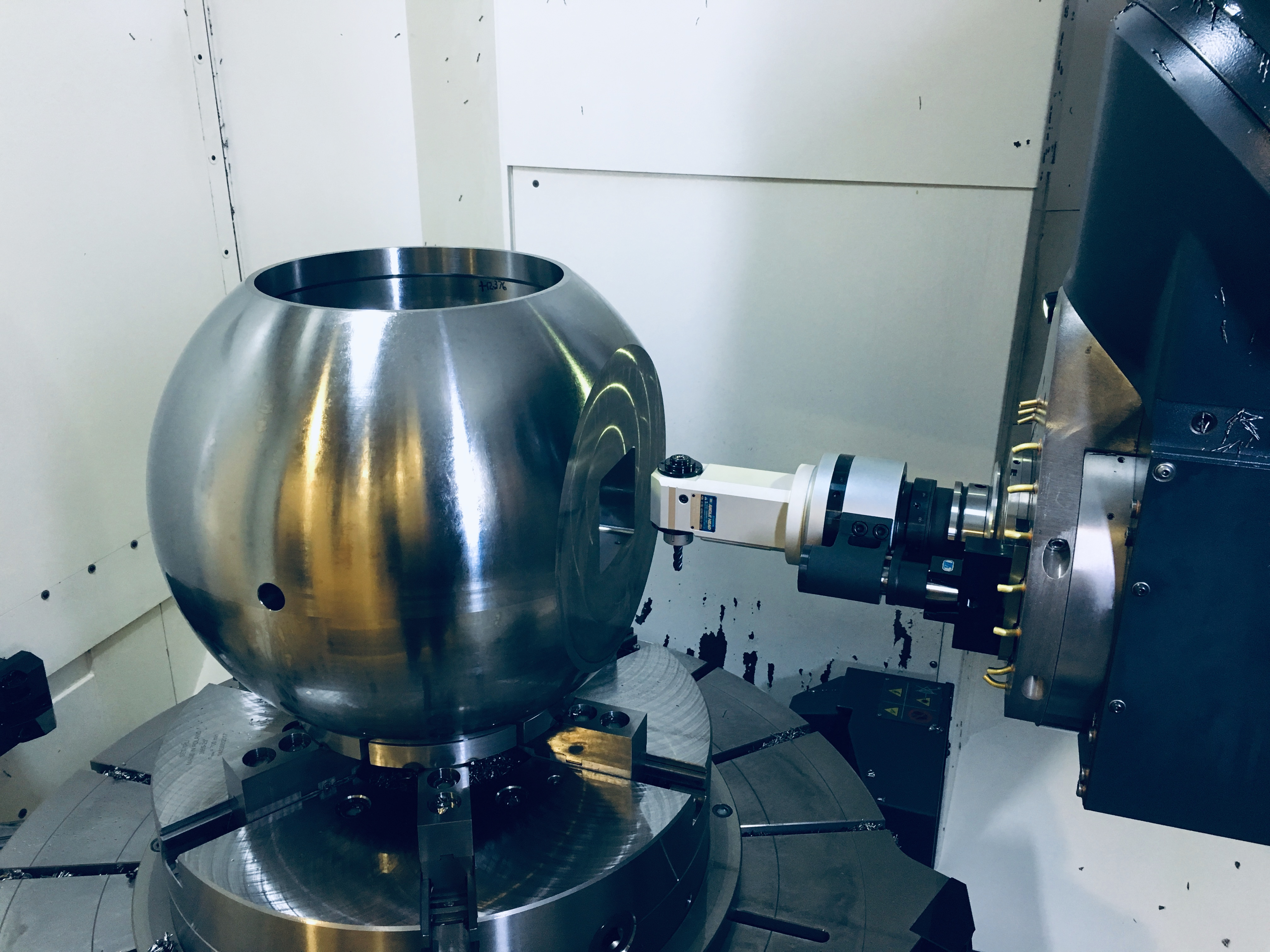 A right angle head entering a hole within a sphere shaped workpiece.